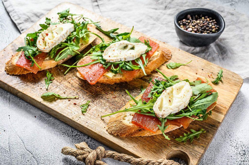 francouzská bageta s kozím sýrem a rukolou na dřevěném prkénku